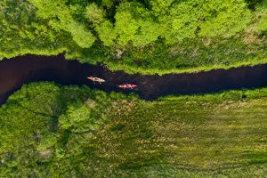Picture of a canoe from a drone on one of the rivers in northern Poland (Kaszuby region near Swornegacie village).